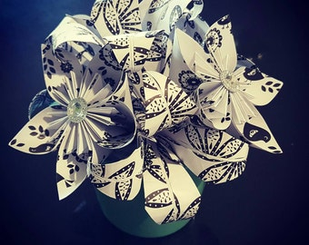White with black pattern florigami flowers and lily's in a green pot with rhinestone centers