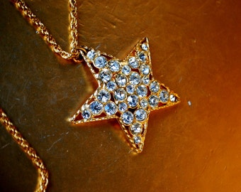 classy vintage 80s gold tone metal necklace with a large  , clear rhinestones star -pendant. Made by Joan River