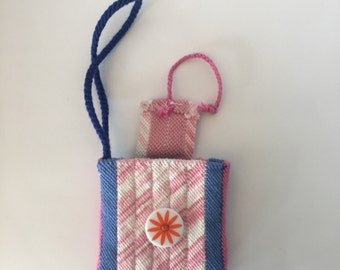 Woven pink, blue, white wristlet with cotton yarn.