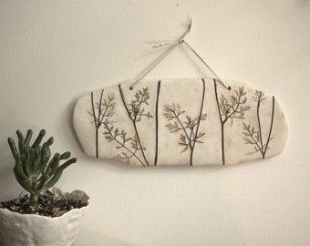 Decorative porcelain wall tile with impression of the leaves of Queen Anne's Lace .  Home decor.
