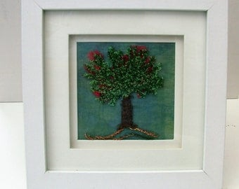 Free style machine embroidery of a tree in blossom in a white box frame.