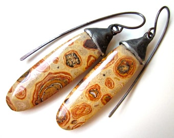 Nobody Would Notice - primitive natural sandy tan orange olive green spotted stone oval & soldered simple black metal bead cap earrings