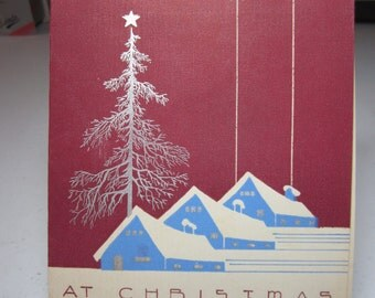 Colorful silver gilded 1930's-40's art deco christmas card shows trio of blue snow topped houses set against a burgundy colored background