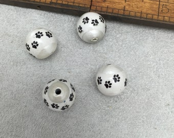 4 dog paw beads  clear glass coat over lays bl ack paw print iage against a pearl  luster background  11 mm