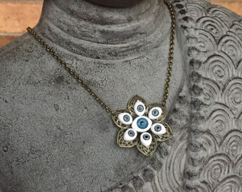 Metal flower with upcycled baby doll eyes necklace