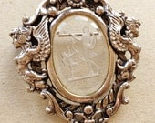 vintage silver tone metal brooch with goddess motif and reversed etched lucite cabochon of mythological design