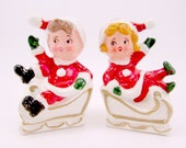 Vintage Christmas Salt and Pepper Shakers Mid Century Ceramic Santa Boy and Girl in Sleighs