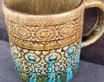 A beautiful brown and turquoise, lace imprint handmade ceramic mug