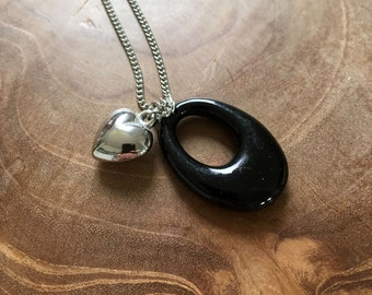 Love Inside - an one of a kind charmnecklace with a black oval and a silver colored heart.