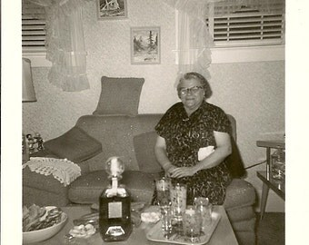 Original 1960s Photograph Older Woman With Large Bottle of Alcohol Party Entertaining