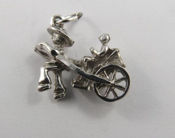 A Sterling Silver Charm of a Man Pulling a Customer Sitting in a Rikshaw.