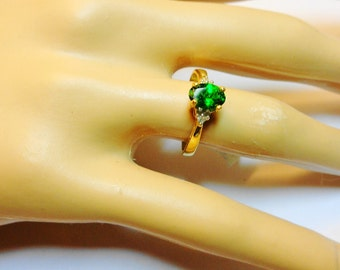 A Natural 7 x 5mm. Tsavorite Oval in a 14kt. Gold Ring with Diamond Accents.