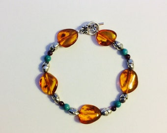 """7.5"""" Semi-Precious Amber, Turquoise, and Garnet Bracelet with silver tone metal spacer beads, and silver leaf toggle clasp"""