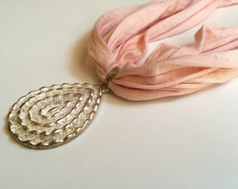 Pink fabric with pendant necklace
