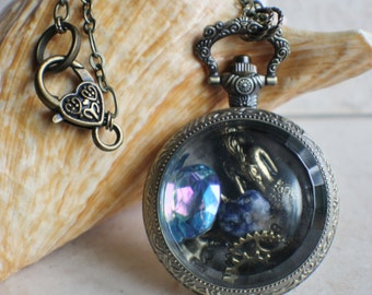 Mermaid pocket watch case locket, filled with mermaid and blue crystal element and charms.