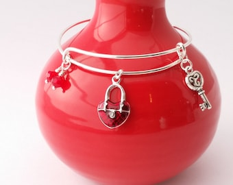 Key to My Heart bangle bracelet featuring red padlock and key charms with red glass faceted beads.