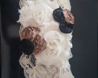 Lace headband with white, black, and champagne colored flowers