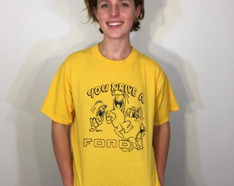 You Drive a Ford! Laughingstock Hilarious Cartoon Drawing Crying Peeing Character Bumper Sticker Yellow Tee T Shirt XL Extra Large 80s 1980s