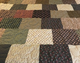 Price reduced.This is a hand sewn quilt featuring old fashioned brown, cream and tan prints