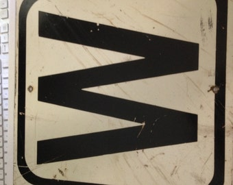 """A square metal """"W"""" sign"""