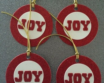 Four Christmas gift tags in red glitter card with JOY on front and gold cord.