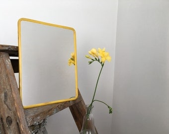 Mirror of Barber vintage, yellow plastic edging.