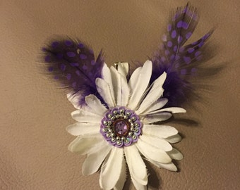 White flower hair clip with purple fearhers and accents