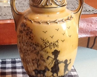 Early mid-century (c.1940s) double-handled vase | urn. Rural profiles of girl, boy and goat on front.  Embossed.  Made in Czechoslovakia.
