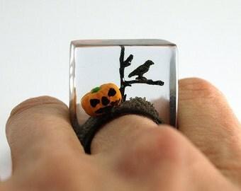 Halloween – Gruseliger Kürbis-Ring mit einem orangen Kunststoff Mini-Kürbis, Ast und schwarzer Krähe auf schwarzen Ring in Gießharz