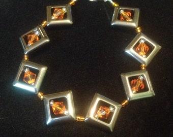 Handmade bracelet made with hermatite diamonds with orange crystal bicone accents