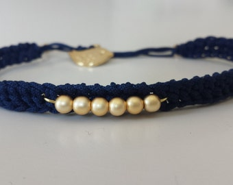 Pulsera tejida a crochet color azul marino y cuentas doradas.