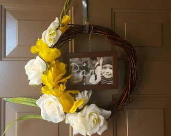 Stunningly unique, custom picture wreath on a wicker frame with beautiful flowers.
