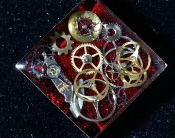 Diamond Shaped Steampunk Pendant, watch parts & gears in resin on a glittery red background DP03