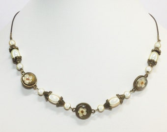 Necklace with cabochons with dried flowers under glass and magic beads
