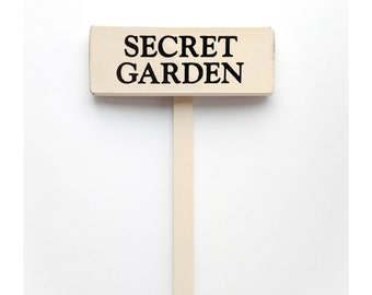 """Garden Stake Sign Saying """"Secret Garden""""  White Wood Sign With Saying in Black Lettering. 7"""" x 2.5"""""""