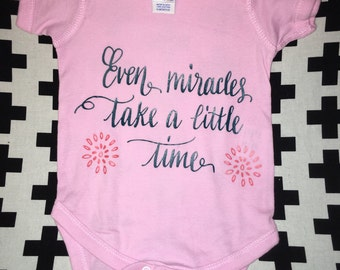 Even Miracles Take  Time Pink Onesie