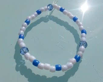 Hand-made elastic bead bracelet with small pearlescent plastic beads in a blue and white pattern