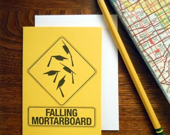 letterpess falling mortarboard greeting card yellow paper with black ink roadside warning sign