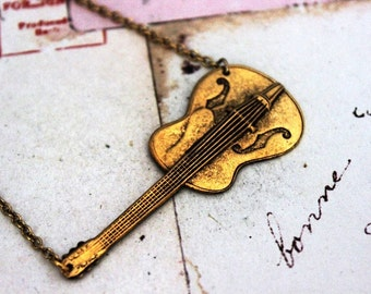 guitar. necklace. gold ox color