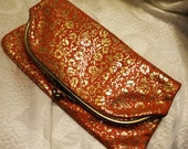 Vintage Orange Leather Fold Over Clutch with Gold Embossed Floral Design and Cream Vinyl Lining Kiss Lock Closure Measures 8 X 8 When Open