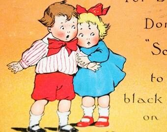 Vintage Halloween Postcard of two little children afraid of a black cat on an orange pumpkin Jack o' Lantern by Tuck 1912 - Damaged