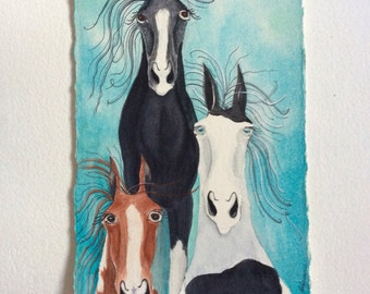 Watercolor print of three colorful  paint horse characters.