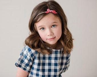 the Avery- a small vintage pink velvet bow attached to a thin nylon headband, hair accessory