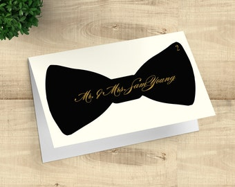 Bow tie tented escort cards, black and gold placecards with faux gold calligraphy; customizable for wedding or any special occasion