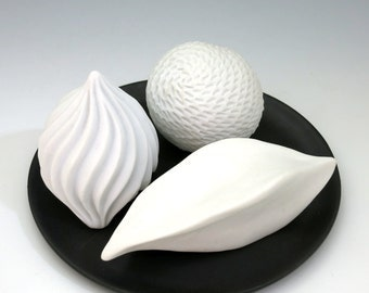 Three white carved porcelain pods on black tray