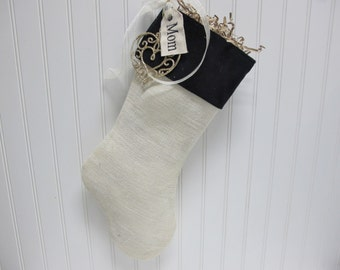 White burlap stocking with black velvet cuff embroidered tag and ornament included