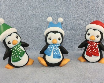 Handpainted ceramic Baby Penguin Trio each penguin wearing a polka dot scarf with a matching santa hat