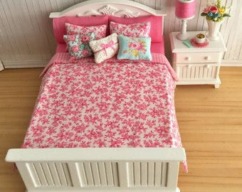 Miniature Bed And Night Stand Set With Beautiful Floral Bedding And Throw Pillows, A Lamp, A Vase Of Flowers, And A Cup Of Tea