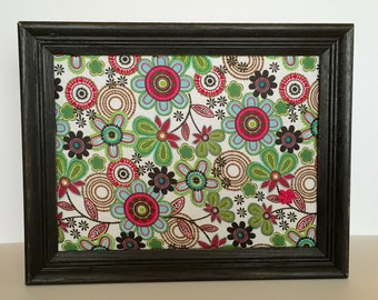 Black framed floral fabric covered bulletinboard