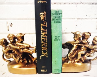 Brass boys tug of war bookends vintage pair library decor librarian book display